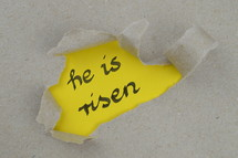 ripped open paper with the words HE IS RISEN