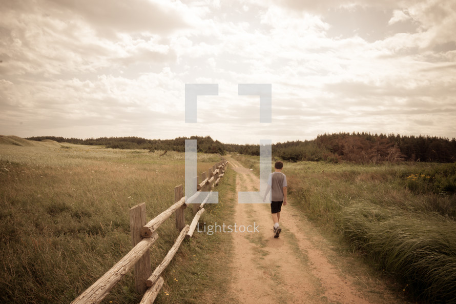 boy walking on a dirt road