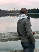 a man looking over a railing across a lake at city buildings