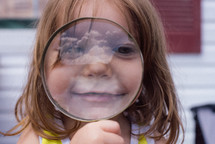a girl looking through a magnifying glass with a reflection of the sky
