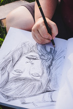 woman sketching on a sketch pad