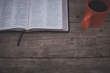 An open Bible and orange coffee mug on wood