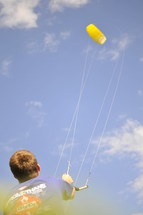 Boy flying a kite.