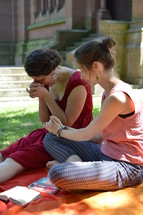 friends praying together sitting outdoors on a blanket next to a cathedral