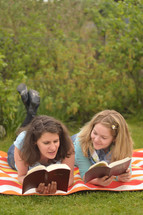 Young women smiling while reading in the bible together laying outside on a blanket in the grass on a sunny summer day.
