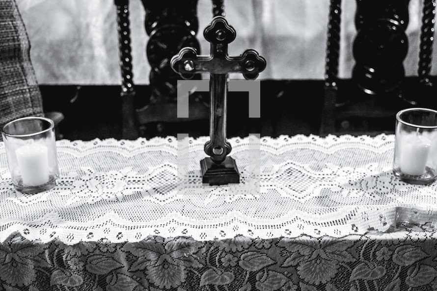 cross and candles on lace runner