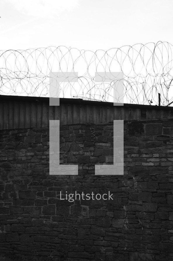 Brick wall with a barbed wire fence.
