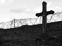 Stone cross in front of a wall with a barb wire fence.