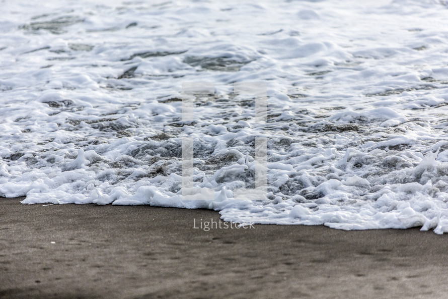 sea foam and tide on the sands of a beach