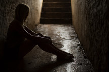 a woman sitting in a hallway in darkness