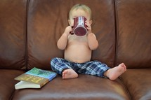 toddler boy sitting on a couch sipping from a mug