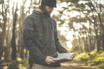 a man reading a Bible alone in a forest
