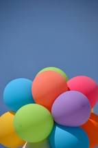 colorful helium balloons in a blue sky