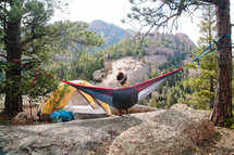 a woman camping sitting in a hammock