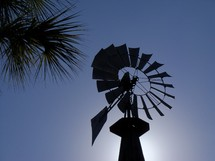 A silhouette of a wind mill standing against the sun and a clear blue sky at sunset next to palm trees on a clear, breezy and cool day.