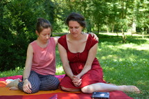 friends praying for each other sitting outdoors on a blanket in a park