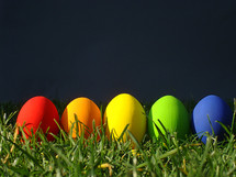 multicolored eggs in the grass in front of a dark gray background.