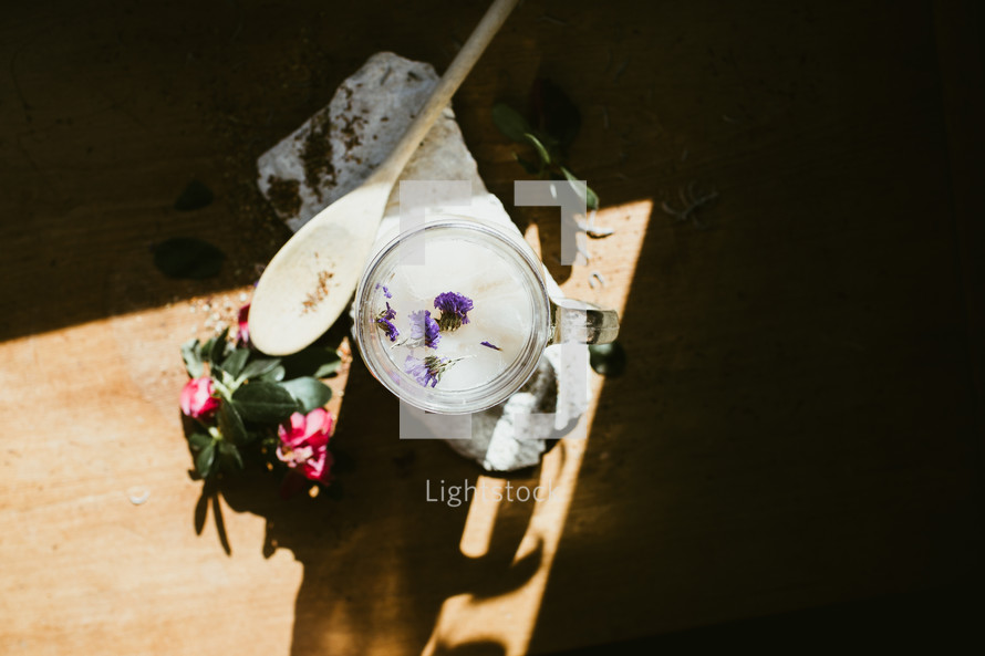 flowers, wooden spoon, and glass mug in a sunspot