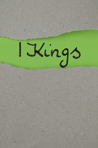 torn open kraft paper over green paper with the name of the book 1 Kings