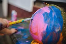 kid painting a pumpkin
