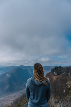 a woman standing on a mountaintop taking in the view