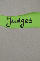 torn open kraft paper over green paper with the name of the book of Judges