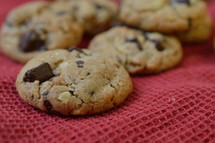chocolate chips cookies on a red cloth