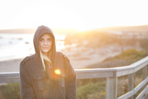 portrait of a woman in a hoodie standing on a shore