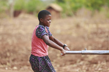 girl plowing a field in Africa