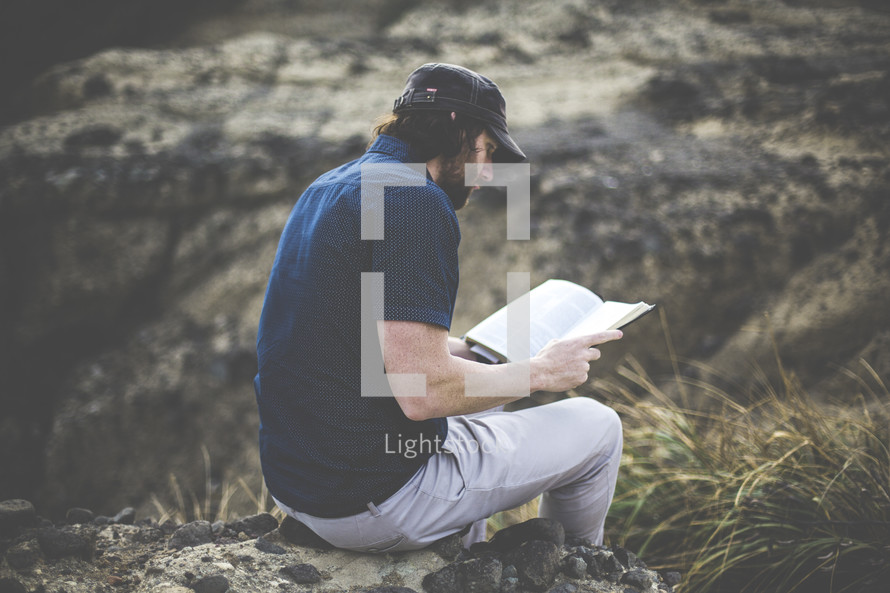 a man sitting on a rock reading a Bible