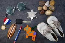 trinkets, medal, sheriff badge, car keys, baby shoes, stones, sunglasses, pencil
