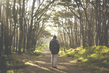 a man standing alone on a path in a forest with a backpack