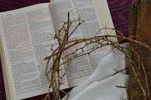 crown of thorns, a piece of cloth, a wooden beam and an open bible