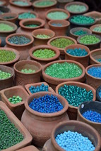 blue and green beads in pottery jars