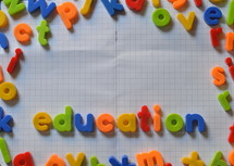 the word education written in colorful magnetic letters on an exercise book.
