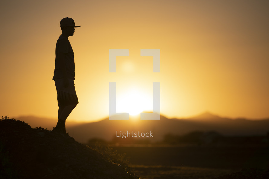 teen boy standing in warm sunlight with arms raised