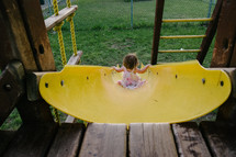a toddler girl going down a slide