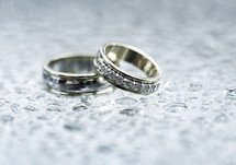 Close up of wedding rings on top of glass table with little puddles from rain drops.