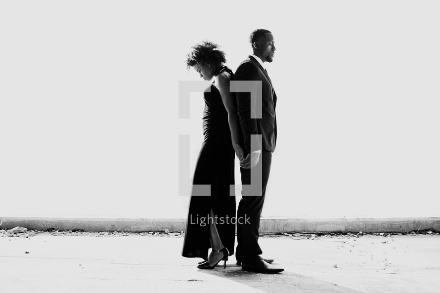 portrait of an African American couple in formal attire standing back to back