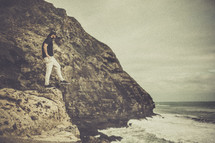 a man balancing on the edge of a rock cliff near the ocean