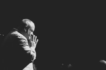 a pastor in prayer during a worship service
