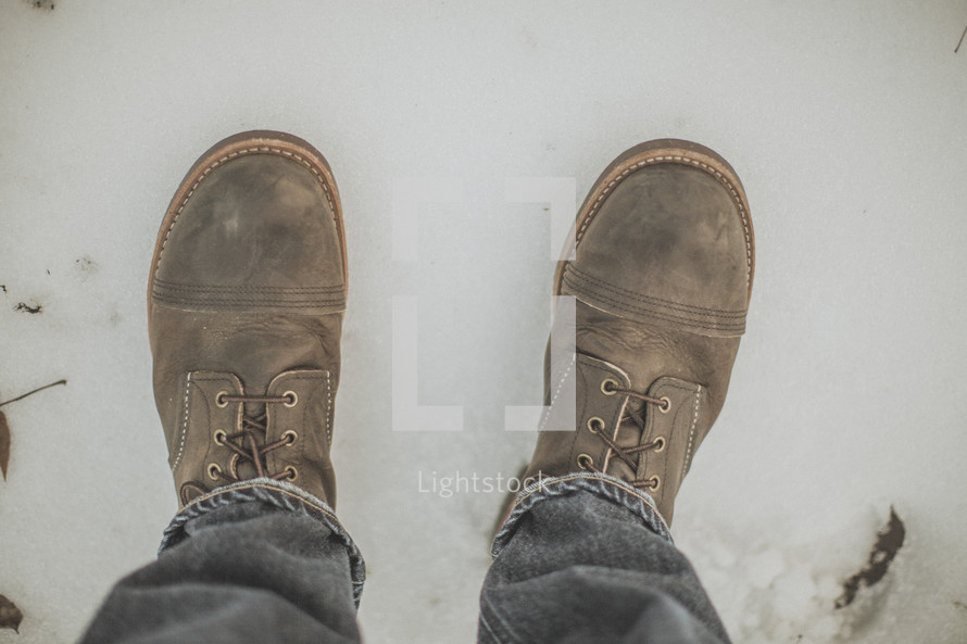 Worn leather boots standing in snow