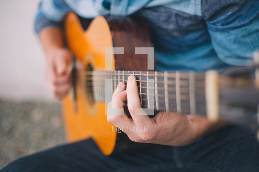 Hands strumming a guitar.