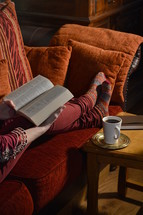 a woman reading a Bible on a couch