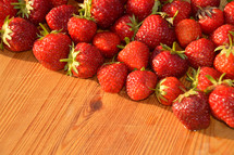 bright red fresh strawberries on a wooden board.
