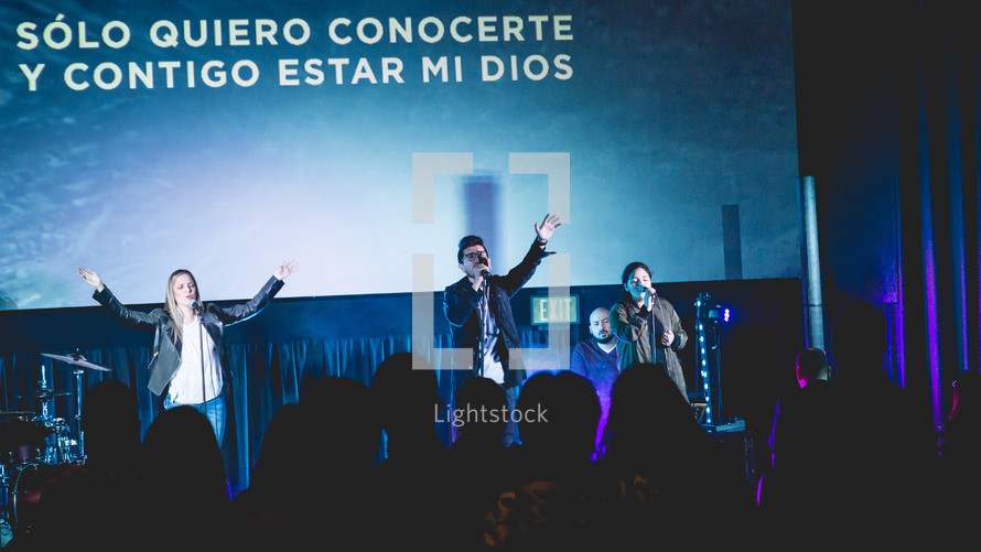 Performers on stage in front of Spanish lyrics on a projection screen