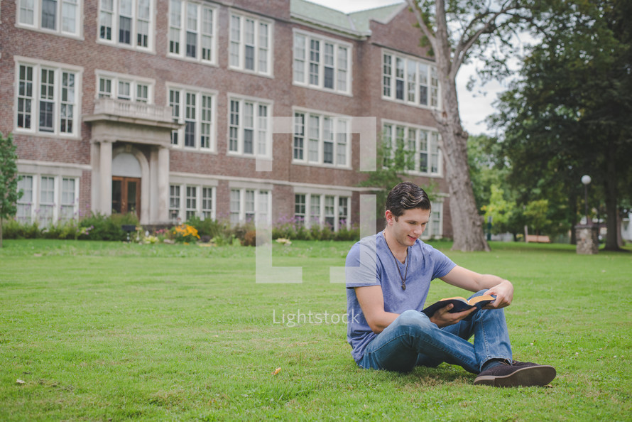 A man reads a Bible on a lawn outside an apartment building.