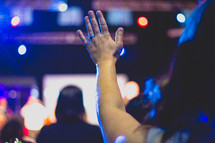 a woman with raised hands during a worship service