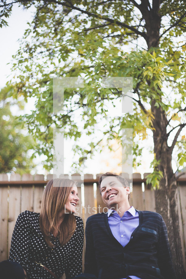 Couple laughing together outside.