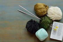 wool and knitting needles on a bible open at the page of Proverbs 31:10-31  The Wife of Noble Character